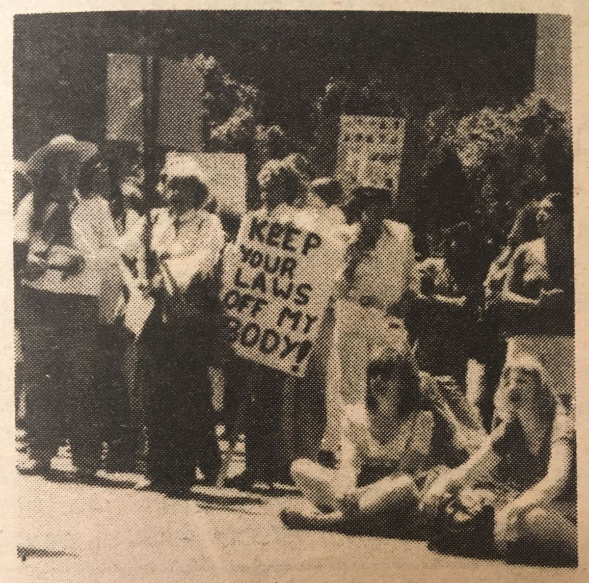"An old photo of a woman at a pro-choice rally in San Francisco holding a sign saying ""keep your laws off my body!"""