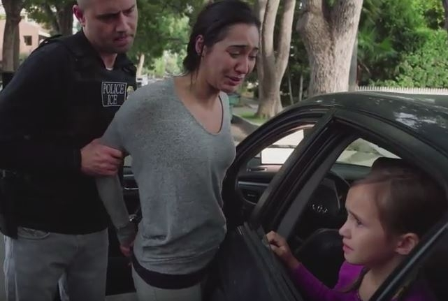A still from the ad, in which an ICE agent forces a mother out of her car while her child watches from the vehicle.