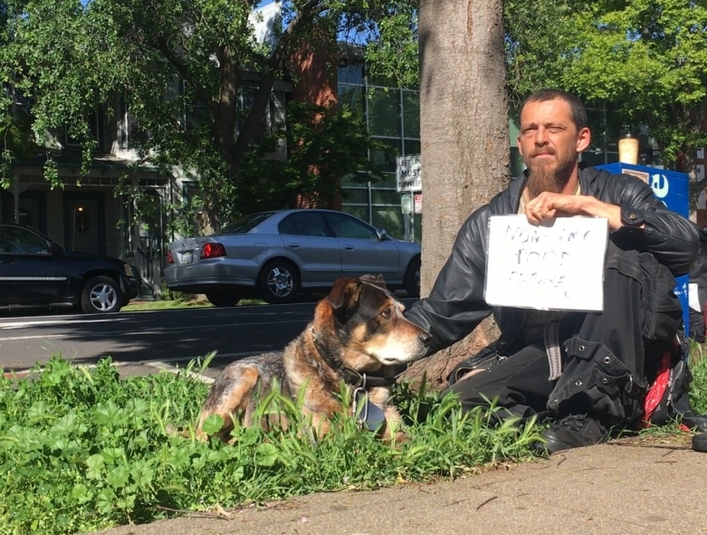 "Plaintiff James ""Faygo"" Clark sits by a Sacramento street corner with a sign and his dog."