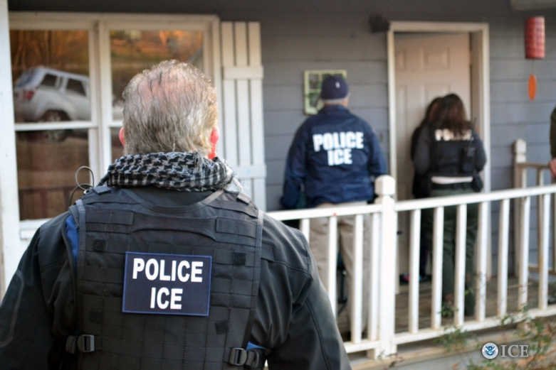 ICE agents standing in front of a home, knocking on the door.