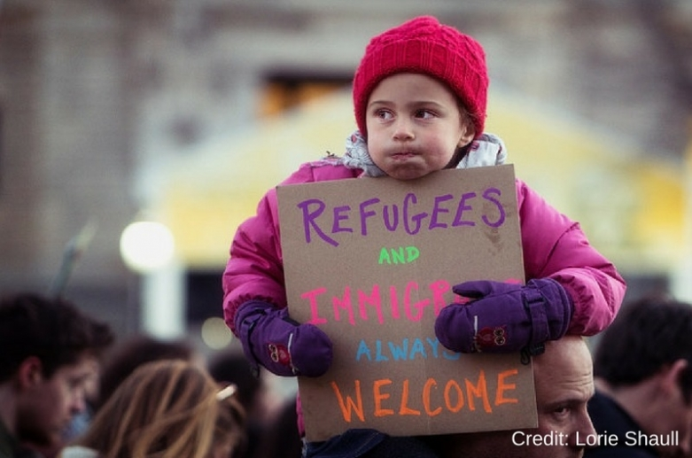 "A small child sits on her father's shoulders at a protest, holding a sign that reads ""Refugees and immigrants always welcome"""