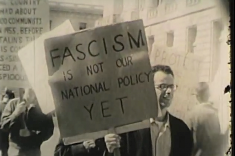 "man holds sign saying ""Fascism is not our national policy yet"""