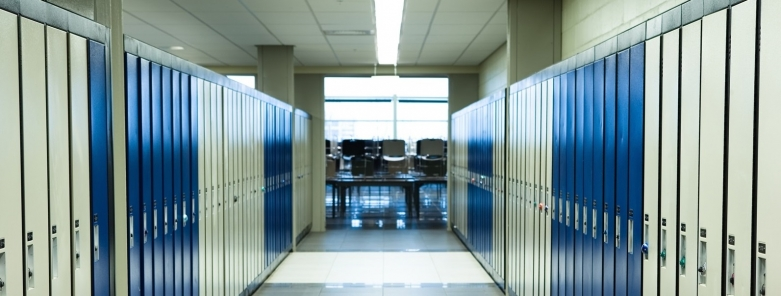 empty school hallway with lockers and an empty classroom at the end