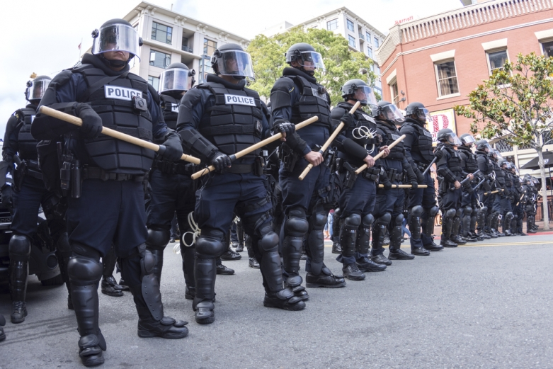 Police in riot gear, holding batons, on a California street