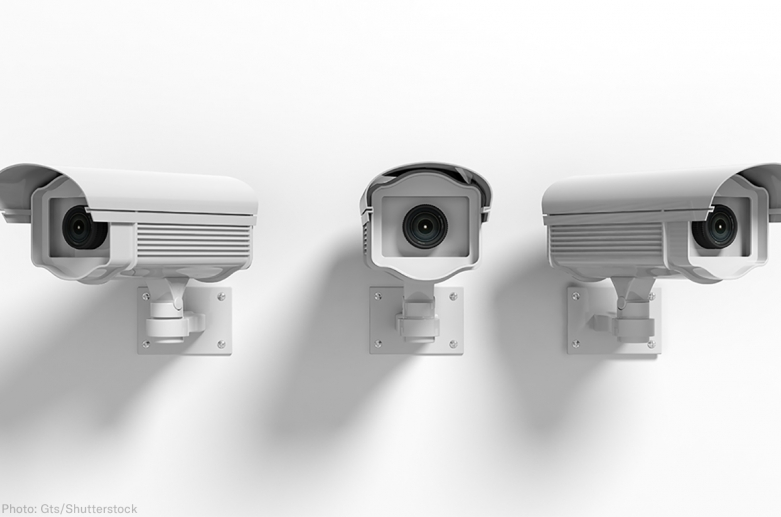 Three surveillance cameras on a wall point in three different directions giving the sense of a panopticon