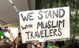 "Sign in a crowd protesting the ban at SFO airport reads, ""We stand with Muslim travelers"""