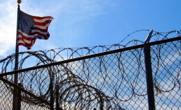 barbed wire fence and american flag
