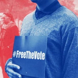 person holding a #freethevote sign in front of a crowd of people