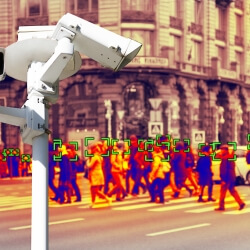 A photograph of surveillance camera in the foreground with a heat map of a gathered crowd in the background.
