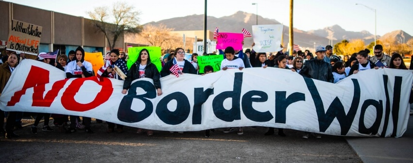 "protesters holding a sign that says ""no border wall"""