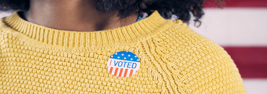 Cropped photo of a woman of color wearing a yellow sweater with an 'I Voted' sticker