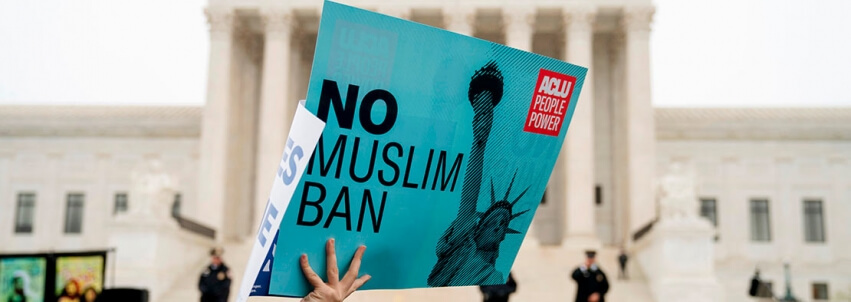 "A person holding a rally poster that says ""No Muslim Ban"" in front of the Supreme Court building"